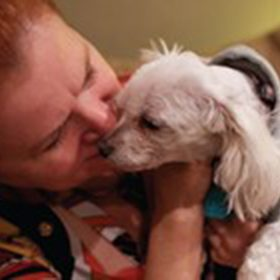 small white dog being cuddled by owner. owner is woman with red hair. dog has on sweater
