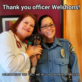 "photo of Veterinarian holding wiener dog next to woman police officer in uniform. both women are smiling at camera. photo reads ""thank you officer welshons! celebrating the fact we will soon have a shelter."""