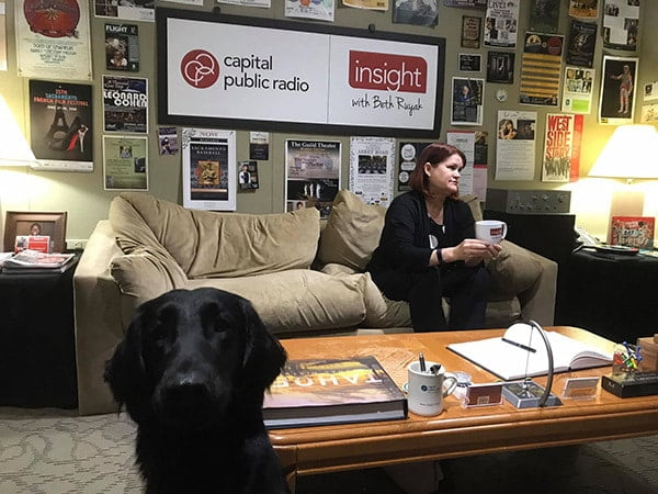 Veterinarian waiting to be on radio. Vet sitting on couch with various posters behind, and things on coffee table. Large black lab looking at camera